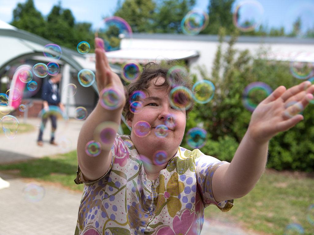 Bildbeschreibung: Eine Junge frau versucht, Seifenblasen mit den Händen zu fangen – am Tag der Begegnung 2020.